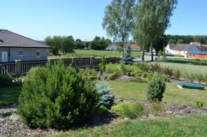 Zahrada s pískovištěm v přední části domu